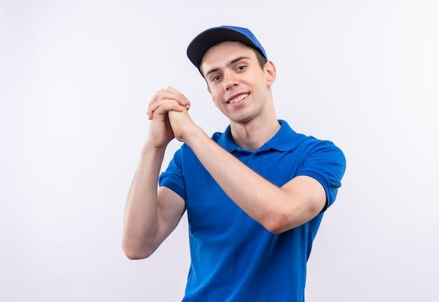 Jonge koerier die blauwe uniform en blauwe pet draagt glimlacht en bedankt