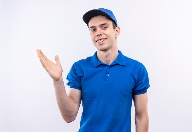 Jonge koerier die een blauw uniform en een blauwe pet draagt die een blij gezicht doet, stijgt de linkerhand