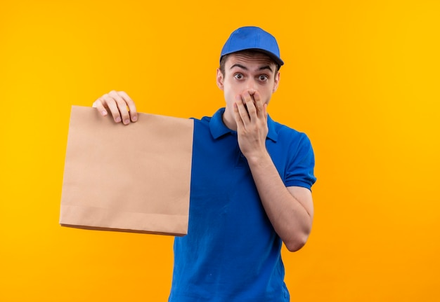 Jonge koerier gekleed in blauw uniform en blauwe pet verrast houdt een zak en sluit zijn muis met de hand
