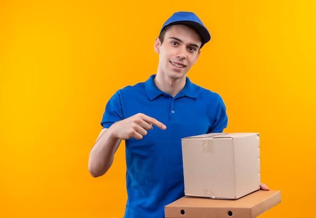 Jonge koerier in blauw uniform en blauwe pet wijst naar de doos