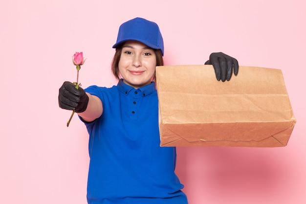 Jonge koerier in blauwe polo blauwe pet jeans houden pakket glimlachend roze reeën op roze