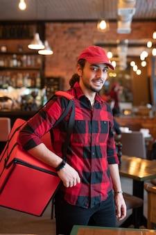 Jonge koerier in rode pet en flanel met grote tas op schouder terwijl hij het restaurant verlaat en bestelde eten aan klanten bezorgt