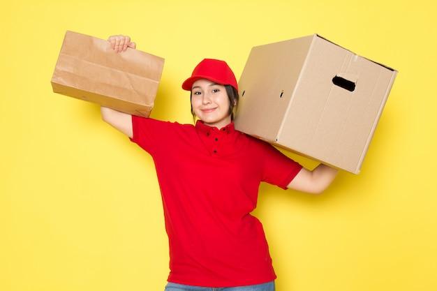 Jonge koerier in rode polo rode dop pakket en doos glimlachend op geel te houden