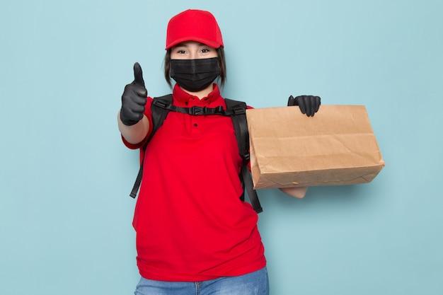 Jonge koerier in rode polo rode dop zwart steriel beschermend masker zwarte rugzak met pakket op blauw