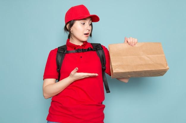 Jonge koerier in rode polo rode pet zwarte rugzak met pakket verrast op blauw