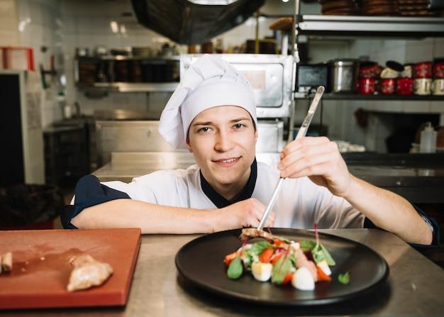Jonge kok die salade met vlees voorbereidt bij lijst