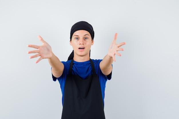 Jonge kok man die gebaar toont in t-shirt, schort en verbaasd kijkt, vooraanzicht.