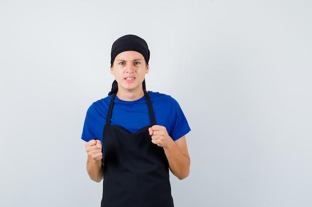 Jonge kok man die gebalde vuisten opheft in t-shirt, schort en woedend kijkt, vooraanzicht.