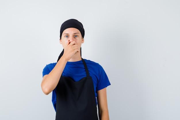 Jonge kok man in t-shirt, schort met hand op mond en perplex kijken, vooraanzicht.