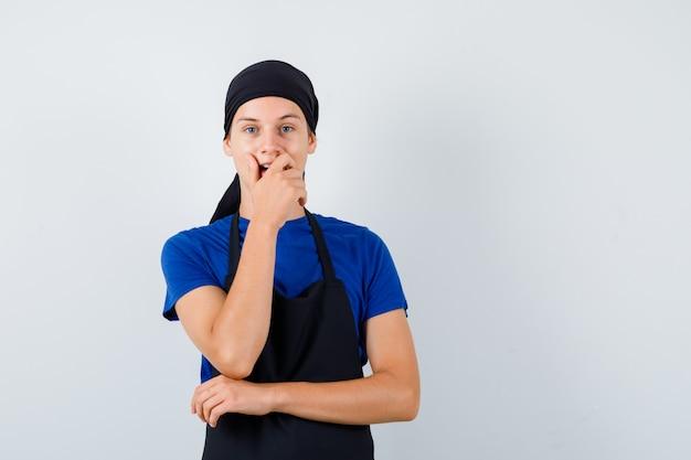 Jonge kok man in t-shirt, schort met hand op mond en verbaasd kijken, vooraanzicht.