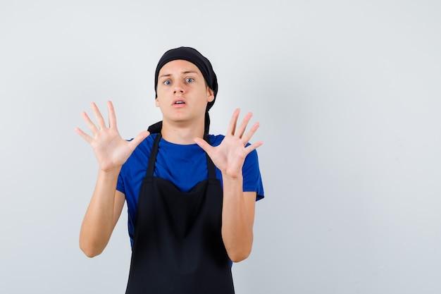 Jonge kok man in t-shirt, schort met handpalmen in overgavegebaar en bang, vooraanzicht.