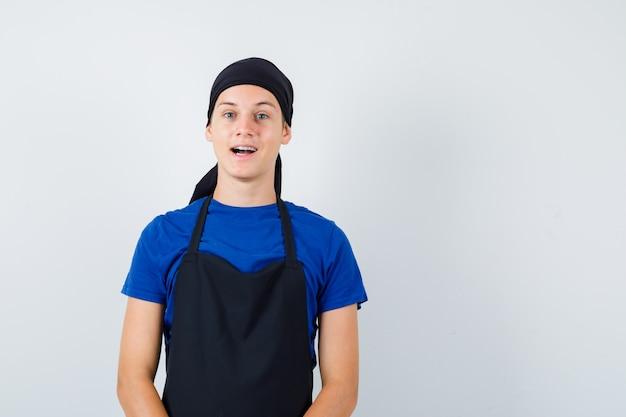Jonge kok man in t-shirt, schort poseren terwijl hij staat en er gelukkig uitziet, vooraanzicht.