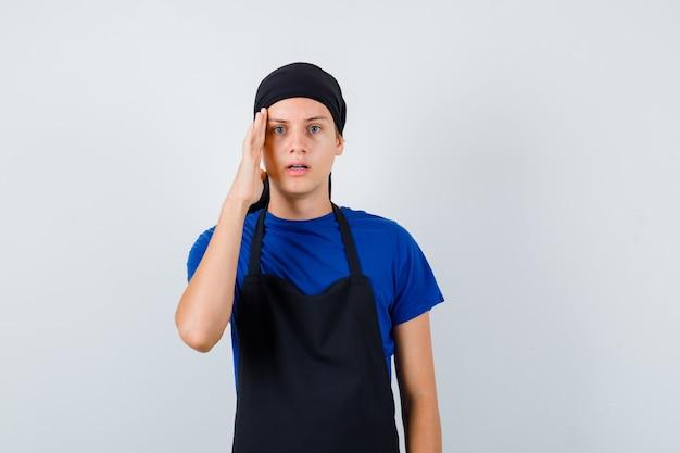 Jonge kok man met hand op hoofd in t-shirt, schort en peinzend kijkend. vooraanzicht.