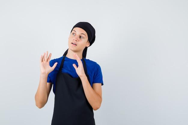 Jonge kok man met handpalmen in overgave gebaar in t-shirt, schort en bang kijken. vooraanzicht.