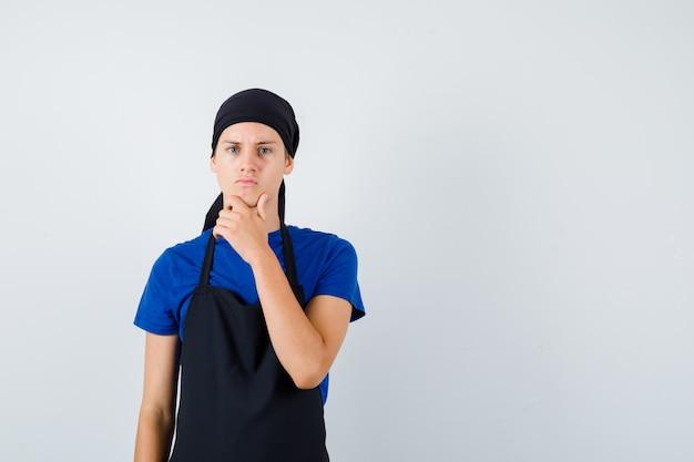 Jonge kok man staande in denkende pose in t-shirt, schort en peinzend, vooraanzicht.