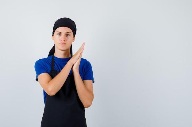 Jonge kok man wrijven handpalmen in t-shirt, schort en serieus kijken. vooraanzicht.