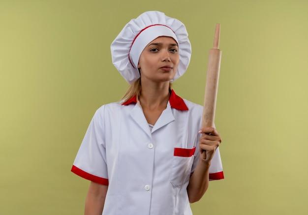 Jonge kok vrouwelijke dragen chef-kok uniforme deegroller op geïsoleerde groene muur met kopie ruimte