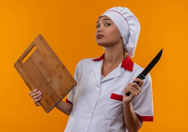 Jonge kok vrouwelijke dragen chef-kok uniforme snijplank en mes houden op geïsoleerde oranje muur