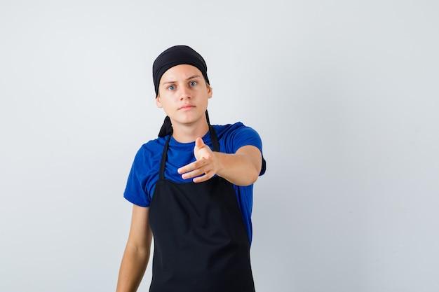 Jonge kok wijst naar voren in t-shirt, schort en ziet er somber uit. vooraanzicht.