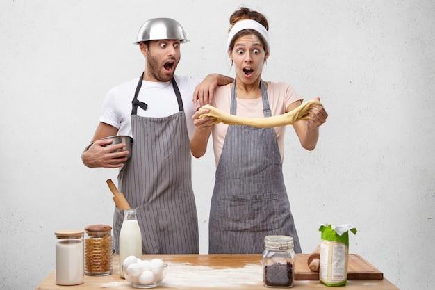 Jonge koks maken reclame voor goede gist, maken deeg, laten de geweldige resultaten zien: gebak is luchtig en elastisch