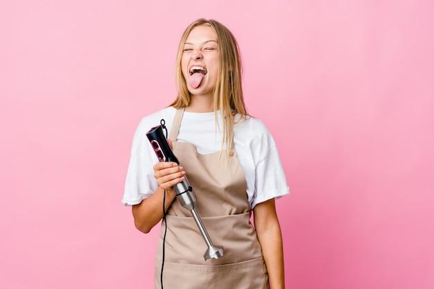 Jonge kokvrouw die een elektrische geïsoleerde mixer houdt