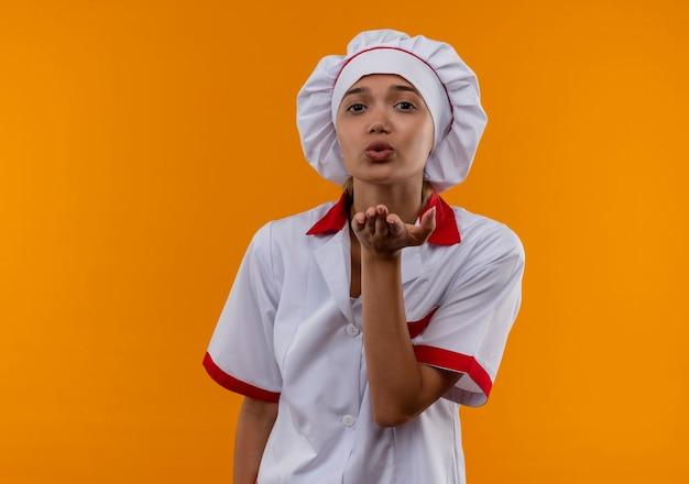 Jonge kokvrouw die eenvormige chef-kok draagt die kusgebaar op geïsoleerde oranje muur met exemplaarruimte toont