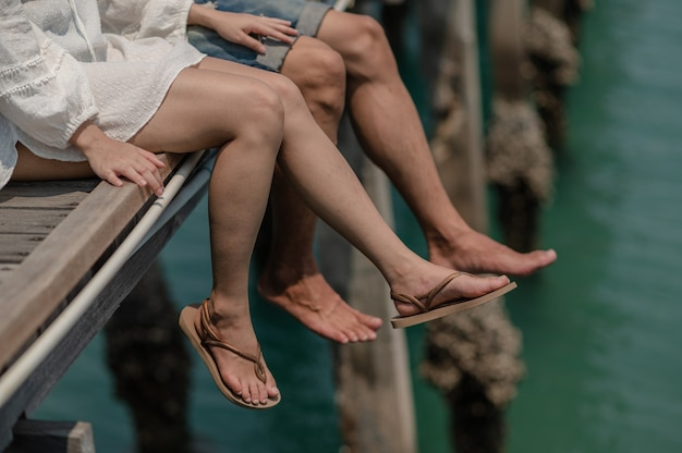 Jonge koppels zitten en omhelzen elkaar op een brug aan zee. zomer verliefd, valentijnsdag concept.