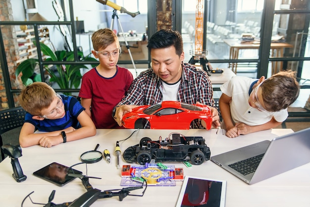 Jonge koreaanse man van elektronica-ingenieur met jonge kinderen met behulp van schroevendraaier te demonteren robotmachine aan de tafel in de moderne school. slow motion