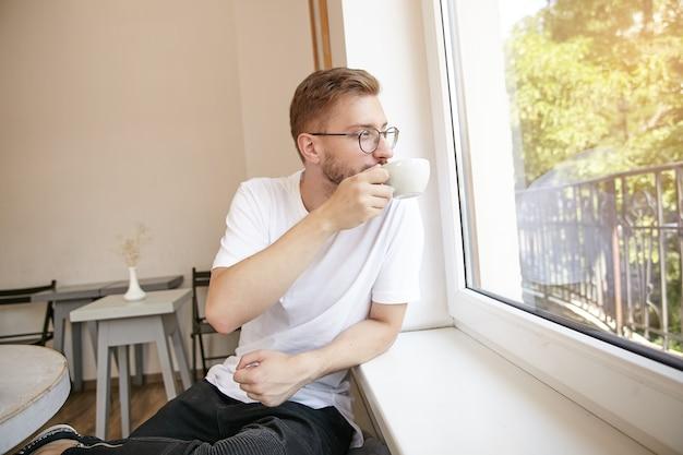 Jonge kortharige aantrekkelijke man in glazen zit naast raam, koffie drinken en genieten van het uitzicht, dromerig en meditatief kijken