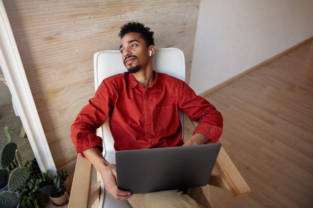 Jonge kortharige, bebaarde man met donkere huid die zijn hoofd op een stoel naar achteren steekt en geniet van uitzicht op het raam terwijl hij pauze heeft met zijn werk, zittend op een beige interieur