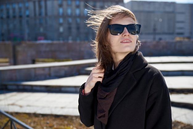 Jonge kortharige vrouw in zonnebril en stijlvolle zwarte jas poseren voor portret op grijze stedelijke stad.
