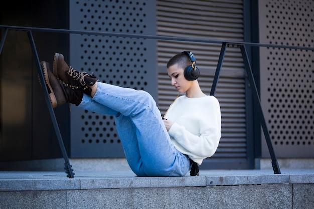 Jonge kortharige vrouw zitten en luisteren naar muziek buitenshuis