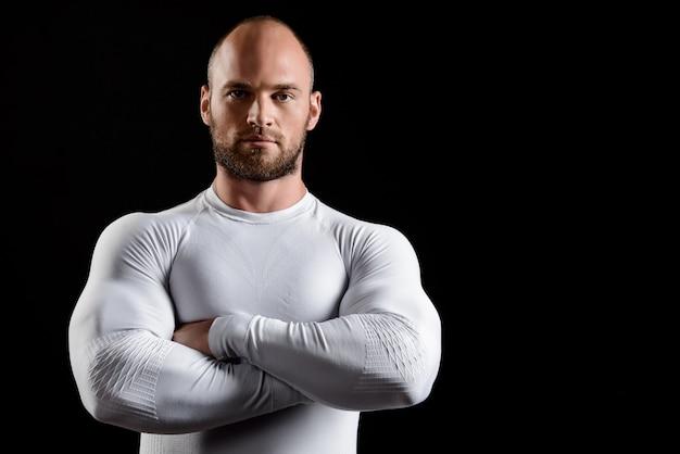 Jonge krachtige sportman in witte kleding over zwarte muur.
