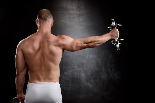 Jonge krachtige sportman training met halters over zwarte muur.