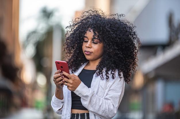 Jonge krullend haarzwarte die gebruikend celtelefoon lopen. sms'en op straat. grote stad.