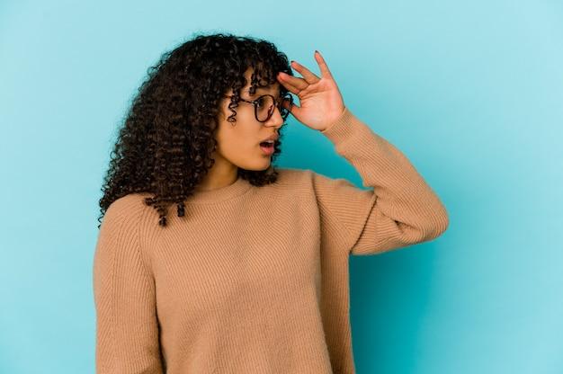 Jonge krullende afro-amerikaanse vrouw geïsoleerd