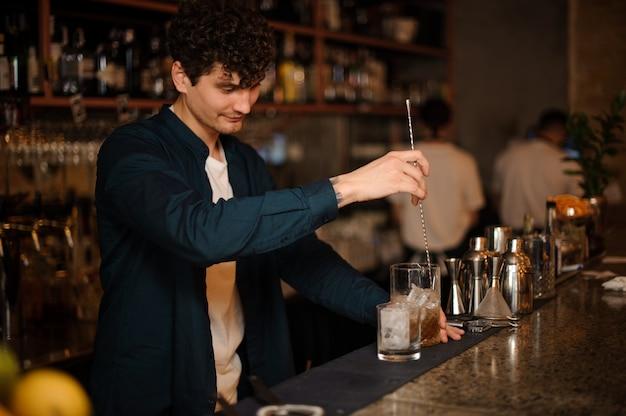 Jonge krullende barman die een verse en zoete drank in het glas in glas beweegt