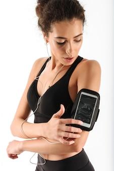 Jonge krullende brunette fitness vrouw luisteren muziek en het gebruik van smartphone
