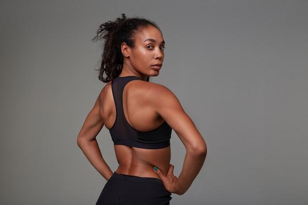 Jonge krullende brunette vrouw met donkere huid kijkt over haar schouder terwijl poseren in atletische zwarte kleding. fitness mannelijk model