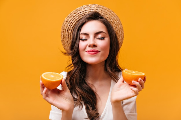 Jonge krullende donkerharige vrouw in schipper houdt sinaasappels en poses met haar ogen dicht.