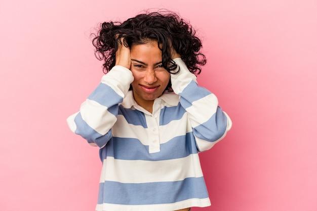 Jonge krullende latijns-vrouw geïsoleerd op roze achtergrond die betrekking hebben op oren met handen.