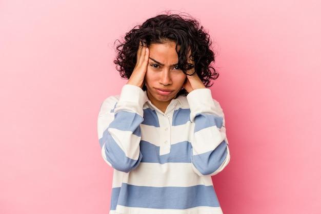 Jonge krullende latijns-vrouw geïsoleerd op roze achtergrond huilen, ongelukkig met iets, pijn en verwarring concept.