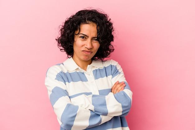 Jonge krullende latijns-vrouw geïsoleerd op roze achtergrond ongelukkig in de camera kijken met sarcastische uitdrukking.