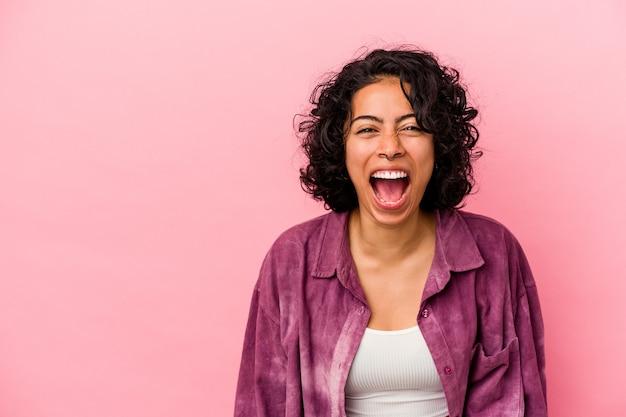 Jonge krullende latijns-vrouw geïsoleerd op roze achtergrond schreeuwen erg boos, woede concept, gefrustreerd.