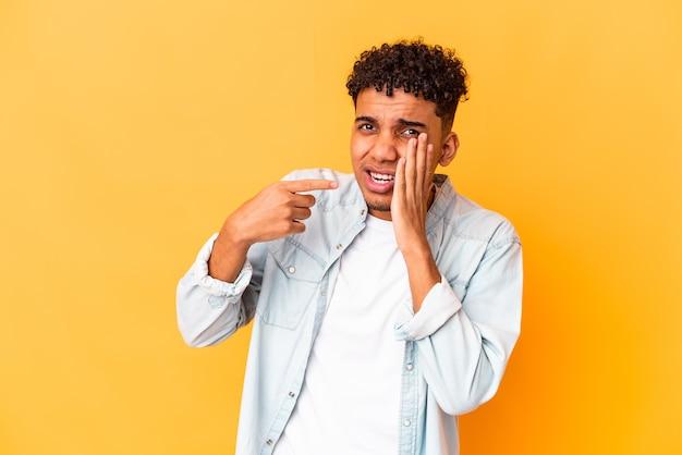 Jonge krullende man geïsoleerd met een sterke tandenpijn, kiespijn