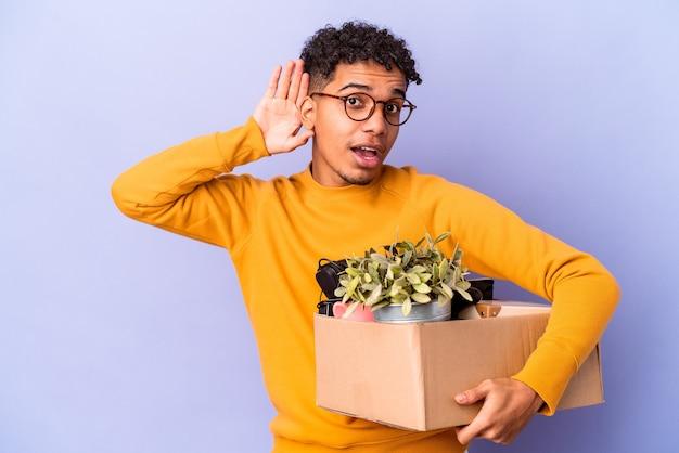 Jonge krullende man geïsoleerd verhuizen naar een nieuw huis proberen te luisteren een roddels