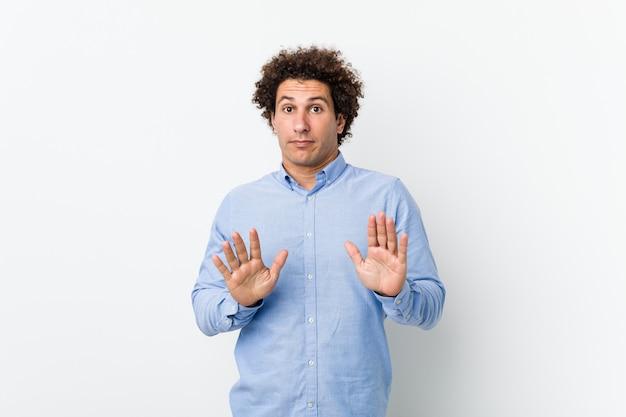 Jonge krullende rijpe mens die een elegant overhemd draagt dat iemand verwerpt die een gebaar van afschuw toont.