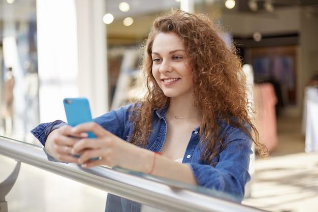 Jonge krullende schoonheid staat in winkelcentrum, telefoon, telefoon in aangename kleur geval houden. persoon drukt vreugde uit omdat