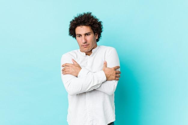 Jonge krullende volwassen man draagt een elegant shirt koud vanwege lage temperatuur