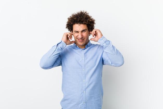 Jonge krullende volwassen man draagt een elegant shirt voor oren met handen.